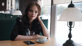 Impatient, young woman looking around and waiting for someone in cafe. Brunette is sitting in a cafe waiting for a. Meeting stock video