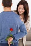 Impatiente Frau, die eine Blume versteckt betrachtet Stockfoto