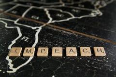 Impeach soletrou com as telhas no mapa do Estados Unidos fotografia de stock