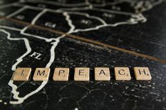 Impeach spelled with  tiles on map of United States stock photography