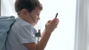 Impedendo asma, bambino nella maschera nebulizzatori con l'aggeggio nelle mani nella sala video d archivio