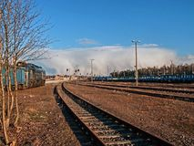 An impending cataclysm. Train standing on the siding, railway tracks, railway station in the distance. In the distance, on the horizon you can see a boiling royalty free stock photo