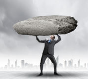 Impending problems. Powerful businessman holding huge stone above head Royalty Free Stock Photography