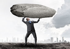 Impending problems. Powerful businessman holding huge stone above head Royalty Free Stock Image