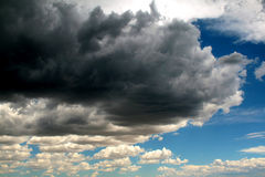 Impending Storm. Dark clouds from, sweeping over bright blue skies stock image