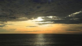 Impending storm. Clouds looming over the Pacific Ocean as sun peeks through before it sets Royalty Free Stock Image