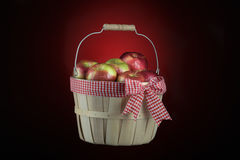 Imperfect apples basket isolated on black and red Royalty Free Stock Image