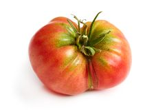 Imperfect heirloom organic tomato. Isolated on white background royalty free stock photo