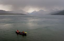 An Imperfect Storm. Photo of some people out on Lake McDonald, Glacier National Park, Montana, USA, in canoe during a thunderstorm. I was amazed they didn't get stock photography