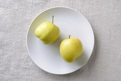 Imperfect ugly misshapen fresh golden apples. Rich in vitamins served on a plate stock images
