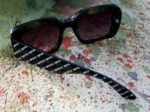 Broken sunglasses with missing handle depicting imperfect nature. In an imperfect world: abstract view of broken sunglasses on a painted concrete base in stock images