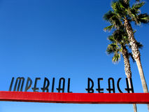 Imperial Beach City Sign. The Imperial Beach city sign on a red cross bar and palm trees welcoming all to enter the city, beach and pier on a warm and sunny Royalty Free Stock Photography