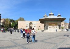 The Imperial Gate of Topkapi Palace and The Fountain. The Sultan Ahmet III fountain is a fountain in a Turkish rococo structure located in the great square in royalty free stock images