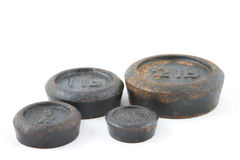 Imperial weights. Antique imperial weights, peeling paint and rust, on white background Royalty Free Stock Images