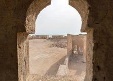 Imperlatura araba antica rovinata, da pesca città Al Jumail, il Qatar Il deserto alla costa del golfo persico Vista dalla finestr immagini stock