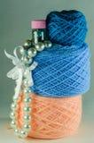 Imperli le perle, il piccolo barattolo con le perle blu, la palla rosa di filato, la palla blu del filato e una piccola palla di  Fotografia Stock