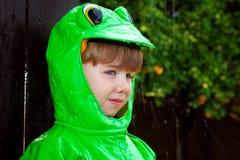 Imperméable de grenouille de garçon avec l'éclaboussement de pluie photographie stock libre de droits