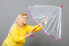Imperméable de port de femme heureuse tenant le parapluie transparent photographie stock