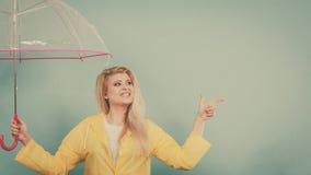 Imperméable de port de femme tenant le pointage de parapluie Photo libre de droits
