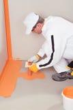 Impermeabilización aplicada cepillo del trabajador en el suelo Imagen de archivo libre de regalías