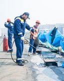 Impermeabilización de los trabajadores de costuras en el puente Imagen de archivo libre de regalías