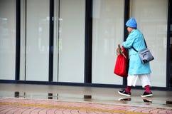Impermeable japonés del desgaste de mujer mayor que camina mientras que llueve tiempo Imagen de archivo libre de regalías