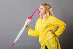 Impermeable que lleva de pensamiento de la mujer que sostiene el paraguas cerrado foto de archivo libre de regalías