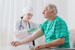 Impfung einer älteren Person Stockbild