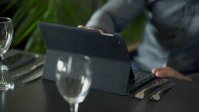 Impianti del giovane con il suo computer portatile nella fine del caffè su archivi video