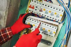 Impianti dell'elettricista con le pinze nello switchbox installazione dell'interruttore fotografia stock libera da diritti