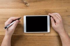 Impianti dell'uomo facendo uso dei dispositivi digitali Sopra la vista di area di lavoro da tavolino fotografia stock libera da diritti