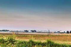 impianti di irrigazione al tramonto nella campagna Fotografie Stock