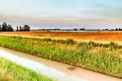 impianti di irrigazione al tramonto nella campagna Fotografie Stock Libere da Diritti