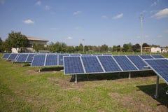 Impianto agricolo a fini energetici elettrico di ecologia con la batteria del pannello solare nella f verde Fotografia Stock