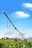 Impianto di irrigazione moderno che innaffia un campo dell'azienda agricola Immagine Stock