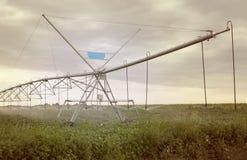 Impianto di irrigazione sul campo verde Immagine Stock