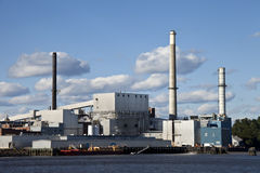 Impianto industriale vicino ad acqua con il cielo blu della nuvola fotografie stock libere da diritti