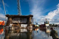Impianto offshore di aggancio al cantiere navale di Danzica con l'uomo del pescatore Fotografie Stock Libere da Diritti