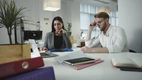 Impiegati che discutono lavoro nell'ufficio considerando computer portatile insieme video d archivio