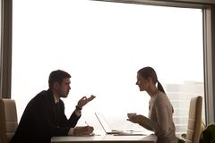 Impiegati che parlano dell'affare allo scrittorio in ufficio Fotografia Stock Libera da Diritti