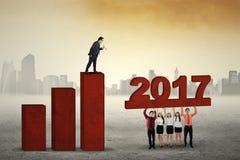 Impiegati che sviluppano grafico finanziario 2017 fotografia stock libera da diritti