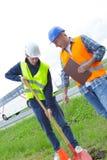 2 impiegati degli uomini che scavano foro in erba Immagine Stock