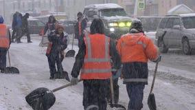 Impiegati dei servizi pubblici in maglie arancio che rimuovono neve dalla strada video d archivio