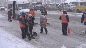 Impiegati dei servizi pubblici in maglie arancio che rimuovono neve dalla strada principale video d archivio