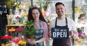 Impiegati dell'uomo e della donna del negozio di fiore che tengono segno aperto e pianta verde video d archivio