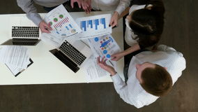 Impiegati di concetto che discutono i diagrammi ed i grafici di profitto archivi video