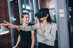 Impiegati di concetto femminili divertendosi sul lavoro che guarda 3d video negli occhiali di protezione di VR, donna che tocca q Immagini Stock