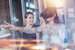 Impiegati di concetto femminili divertendosi sul lavoro che guarda 3d video negli occhiali di protezione di VR, donna che tocca q Immagine Stock