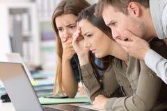 Impiegati preoccupati che leggono cattive notizie sulla linea Fotografia Stock