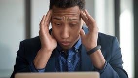 Impiegato afroamericano stanco che soffre dall'emicrania facendo uso del computer portatile fotografia stock libera da diritti